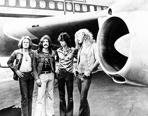 Led Zeppelin stands beneath wing of their plane Starhip One. (1-r) John Paul Jones, John Bonham, Jimmy Page, Robert Plant. July 1973.