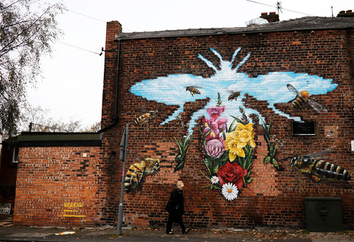 A woman walks past steet art showing bees, the city's symbol, in Manchester