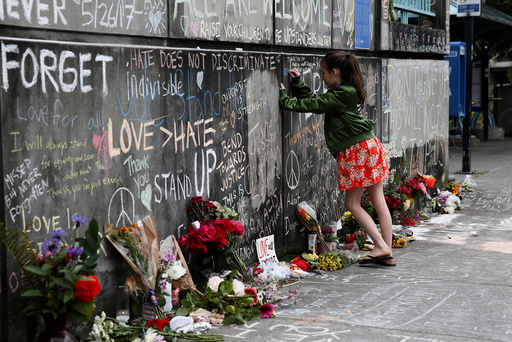 A girl leaves a message at a makeshift memorial for two men who were killed on a commuter train while trying to stop another man from harassing two young women who appeared to be Muslim, in Portland