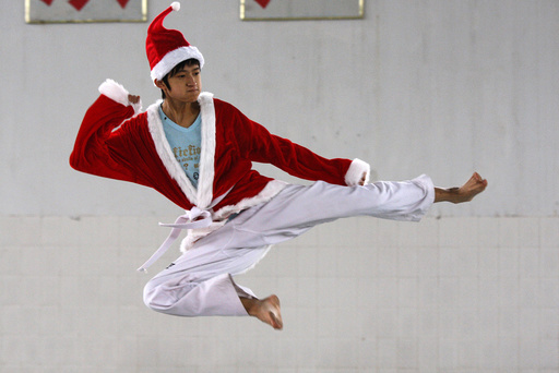 A student dressed in a Santa Claus costume to celebrate Christmas, practises taekwondo at a sports school in Suining