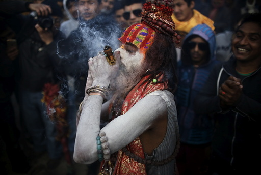 A Hindu holy man, or sadhu, smeared with ashes smokes marijuana in a chillum during the Shivaratri festival in Kathmandu
