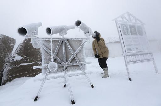 A woman looks through a telescope covered with hoarfrost near Krasnoyarsk