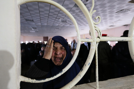 Palestinian woman reacts as she asks for a travel permit to cross into Egypt through the Rafah border crossing in Rafah in the southern Gaza Strip