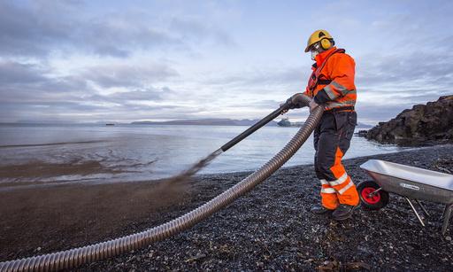 Bark sprøytes på stranda for å innkapsle den simulerte oljen under oljevernøvelsen Øvelse Svalbard onsdag.