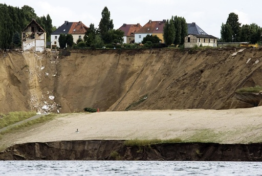 A crumbling house sits on the edge of a cliff following a landslide in the village of Nachterstedt