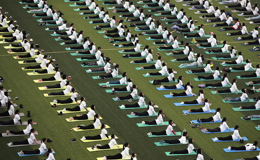 Hundreds of participants practice yoga at a charity event to mark the upcoming World AIDS Day, at an university in Guilin
