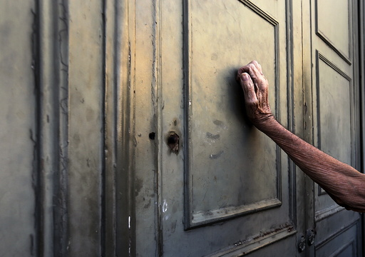 A pensioner leans against the main door of a branch of the National Bank in Athens