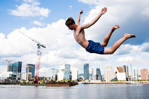 Kim Morten Buer (18) hopper i havet på en av årets varmeste sommerdager på Sørenga i Oslo torsdag ettermiddag.