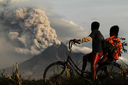 Boys look at the eruption of Mount Merapi volcano in Manisrenggo village
