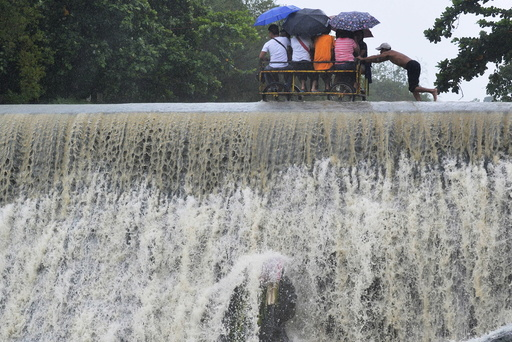 Residents cross a swelling dam, due to rising waters brought about by Typhoon Koppu, in Las Pinas city, metro Manila