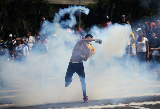 A demonstrator throws back a tear gas canister during clashes with security forces at an opposition rally in Caracas