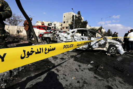 Syrian army soldiers and civilians inspect the site of a suicide bombing at a police officers' club in a residential district of Damascus, in Masaken Barza