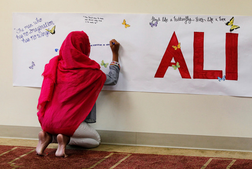 A member of the Louisville Islamic Center writes messages on a memorial banner as she pays her respect to Muhammad Ali, the former world heavyweight boxing champion after he died at the age of 74 on Friday at the Islamic Center in Louisville