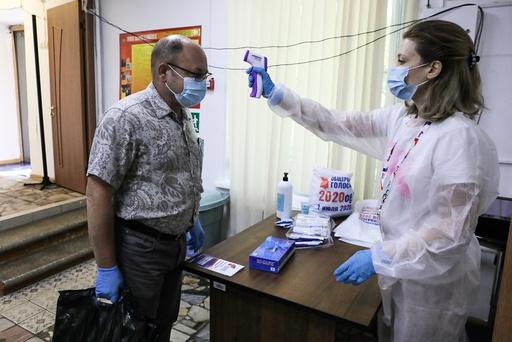 En mann blir sjekket for feber ved et valglokale i Russland under folkeavstemningen i forrige uke. Antall nye smittetilfeller fortsetter å stige i Russland. Foto: AP / NTB scanpix