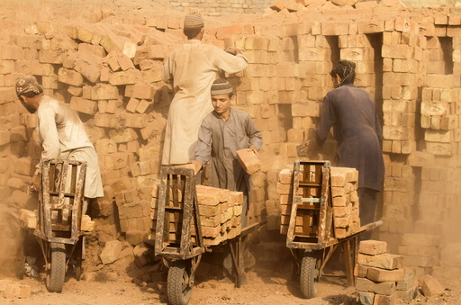 Laborers move baked bricks from an oven at a kiln on outskirts of Peshawar