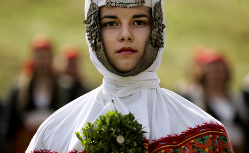 Bulgarian woman dressed in a traditional wedding dress participates in the Rozhen folklore festival in the Rhodope mountains