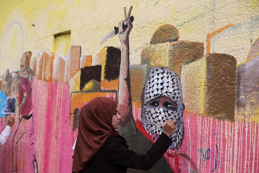 Palestinian woman paints a mural, depicting a masked Palestinian holding a knife, in support of Palestinians committing stabbing attacks against Israelis, in Rafah in the southern Gaza Strip