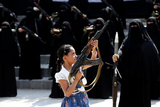 Girl holds a rifle in front of women loyal to the Houthi movement taking part in a parade to show support to the movement in Sanaa, Yemen