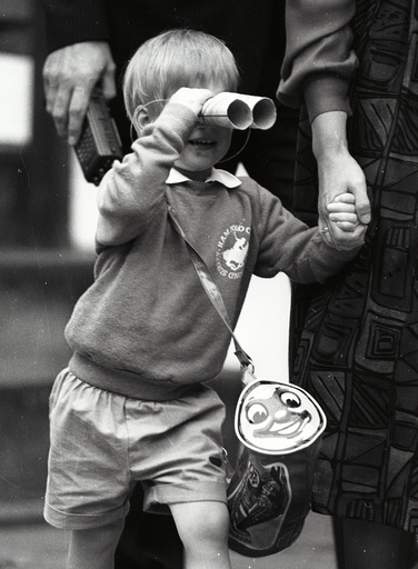 Prince Harry looks through a pair of toy binoculars he made on his first day at kindergarten