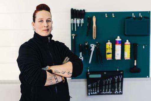 Portrait of confident female mechanic standing arms crossed in auto repair shop