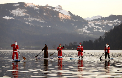 People dressed as Santa Claus pose on their stand-up paddles as they cross Lake Aegerisee near Oberaegeri