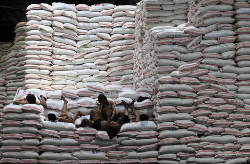 Workers take a break atop sacks of rice piled inside a warehouse of National Food Authority (NFA) in Taguig city