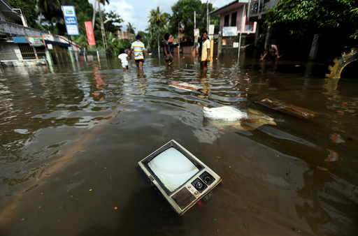 A TV set floats on a flooded road in Dodangoda village in Kalutara