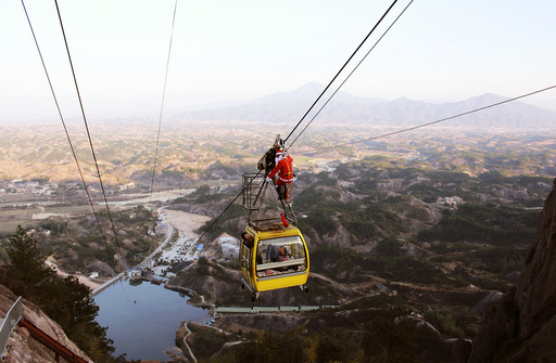 A staff of Shiniuzhai scenic zone dressed as Santa Claus stands on top of a cable car to send gifts to visitors, in Pingjiang