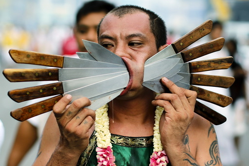A devotee of the Chinese Samkong Shrine walks with knives pierced through his cheeks during a procession celebrating the annual vegetarian festival in Phuket