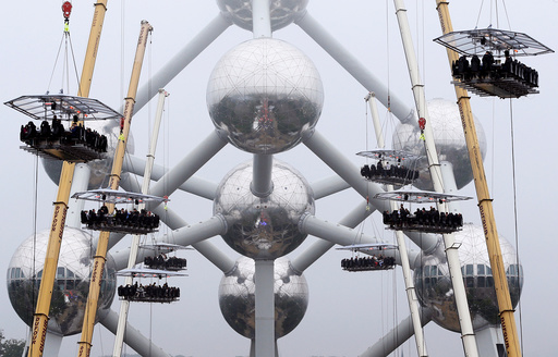 Guests sit at tables suspended from cranes at a height of 40 metres in front of the Atomium, as part of the 10th anniversary of the event known as Dinner in the Sky, in Brussels