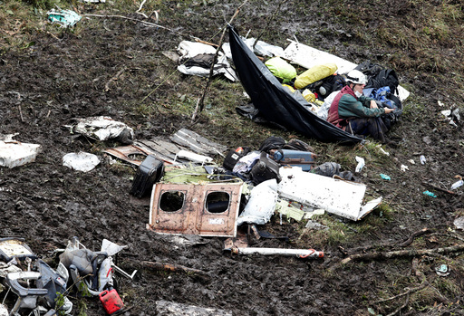 A rescue worker sits near the wreckage of a plane that crashed into the Colombian jungle with Brazilian soccer team Chapecoense onboard near Medellin