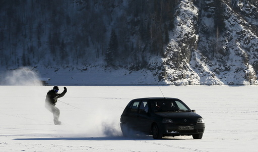 Car tows snowboarder along frozen surface of Yenisei River in Taiga district outside Krasnoyarsk