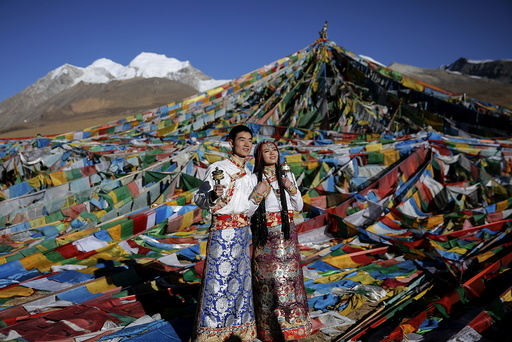 Jing Li (L) and her husband Ke Xu wear Tibetan traditional costumes as they pose for their wedding photos at the Nianqing Tanggula mountain pass in the Tibet Autonomous Region,