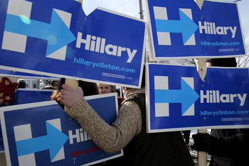 U.S. Democratic presidential candidate Hillary Clinton greets campaign volunteers holding signs while going to door-to-door to greet voters in a neighborhood in Manchester