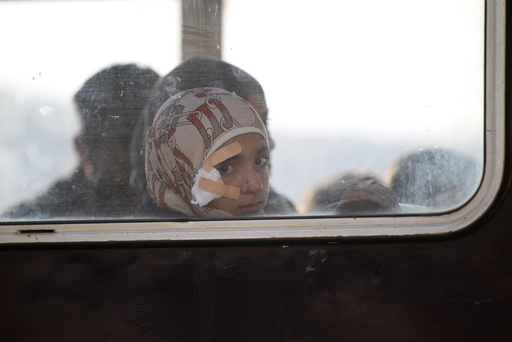 A girl sits in bus evacuating fighters and civilians from two besieged Shi'ite towns of al-Foua and Kefraya in mainly rebel-held northwestern province of Idlib, as they wait to cross to Turkey from the Syrian-Turkish border crossing of Bab al-Hawa