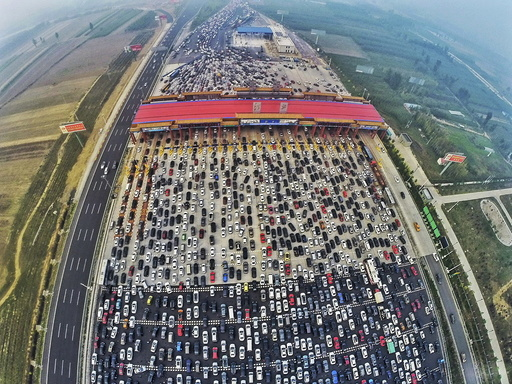 Vehicles are seen stuck in a traffic jam near a toll station as people return home at the end of a week-long national day holiday, in Beijing
