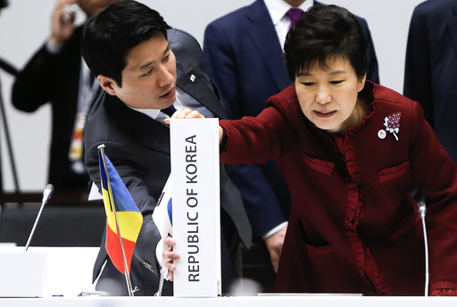 South Korea's President Park Geun-hye adjusts the country placeholder during the Asia-Europe Meeting (ASEM) in Milan