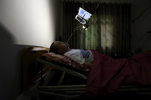 Xu, suffering from physical disability after a severe spine injury, uses an extended stylus to type on a tablet as he runs his online store on his bed, in Houwu village of Quzhou