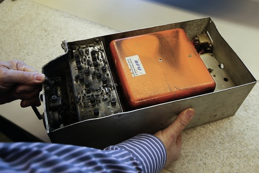 An employee of Germany's Bundesamt fuer Fluguntersuchung BFU holds a historic and partly burned tape-based voice recorder at their headquarters in Braunschweig