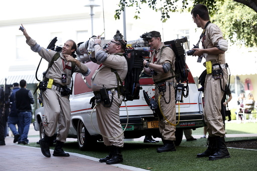 Enthusiasts wearing Ghostbusters costumes stand by an ECTO-1, the vehicle used in the upcoming movie
