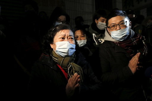 A woman prays for her relatives who were inside a 17-storey apartment building which collapsed after an earthquake hit Tainan, southern Taiwan