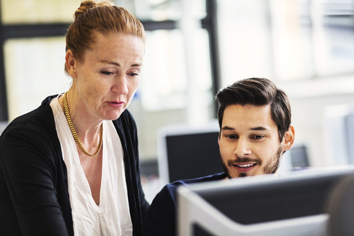 Businesswoman with male colleague using computer in office