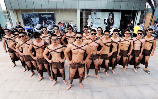 Male fitness instructors and students dressed in costumes of Spartan warriors pose during the one-year anniversary for Juicedaily, in front of a shopping mall in Xuzhou
