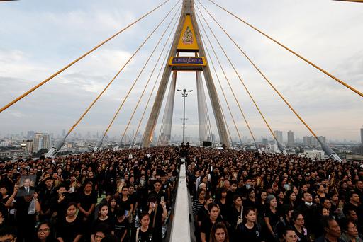 People gather during an event to mark late Thai King Bhumibol Adulyadej's birthday at Bhumibol Bridge over Chao Phraya river in Bangkok