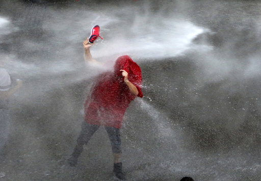 A Lebanese protester is sprayed with water during a protest against corruption and rubbish collection problems near the government palace in Beirut
