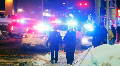 Police officers are seen near a mosque after a shooting in Quebec City