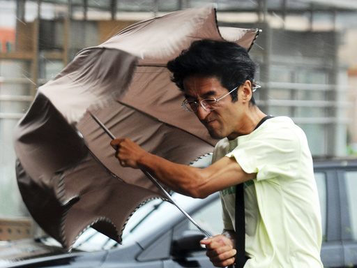 A man holds onto his umbrella against strong wind and heavy rainfalls on a street as Typhoon Haikui hit Shanghai