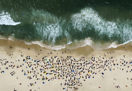 People enjoy the sunny weather at Ipanema beach in Rio de Janeiro