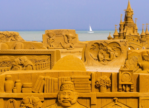A sailing boat is seen behind sand sculptures during the Sand Sculpture Festival Frozen Summer Fun in Ostend