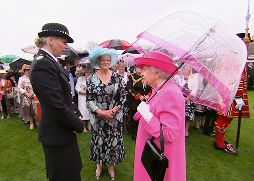 Still image of Britain's Queen Elizabeth speaking to Commander Lucy D'Orsi during a garden party at Buckingham Palace in London